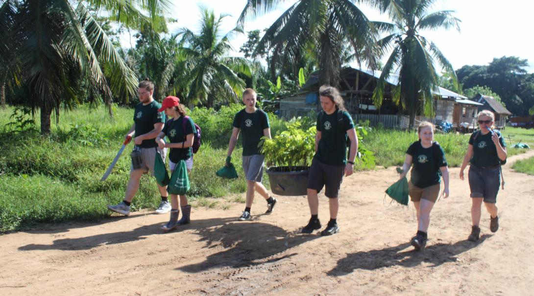 Voluntarios llevando materiales a la granja durante su voluntariado de conservación en Perú